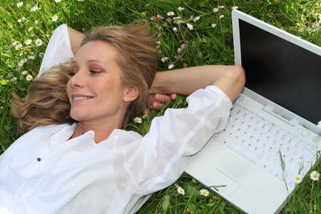 Pretty lady lounging in the grass next to laptop computer