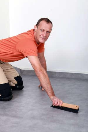 Man smoothing carpet