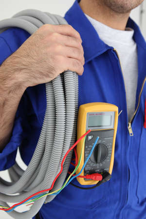 Cropped shot of an electrician with a roll of cable and a voltmeter in his pocket