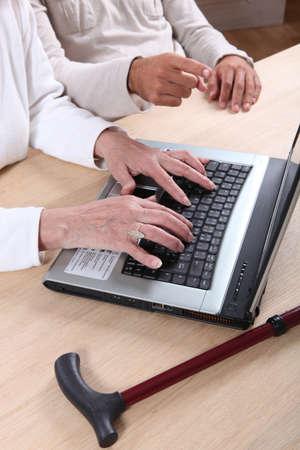 Senior woman tapping a computer keyboard
