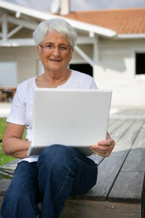 Senior woman using her laptop outdoors