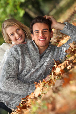 Couple laid in fallen leaves
