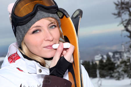 Attractive skier applying lip balm
