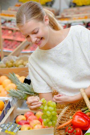 Photo pour Woman choosing a bunch of grapes - image libre de droit