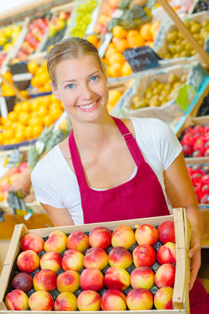 Photo pour Woman holding a crate of fruit - image libre de droit