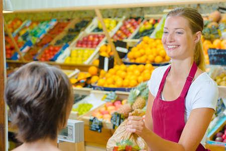 Photo pour Greengrocer serving a customer - image libre de droit