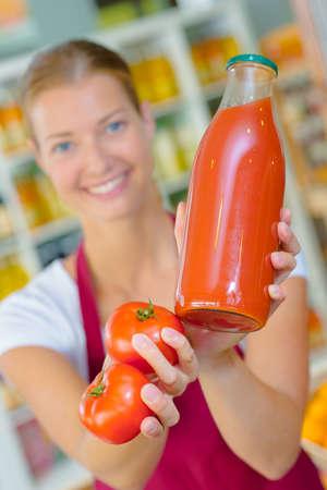 Photo pour Woman holding a bottle of tomato juice - image libre de droit