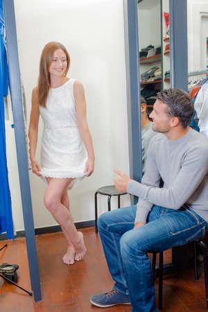 Helping his girlfriend choose a dress