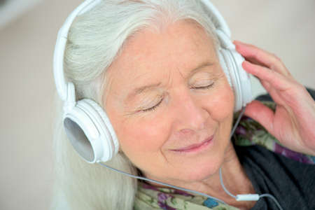 Foto per Old lady with headphones on - Immagine Royalty Free