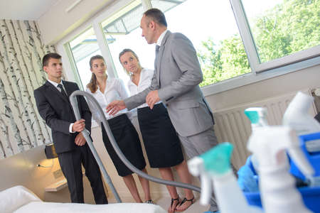 Supervisor with team of cleaners in hotel room