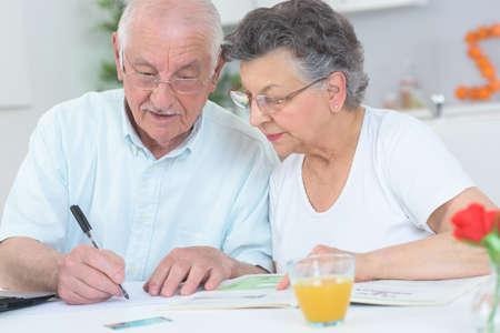 Foto de Elderly couple looking at magazine and taking notes - Imagen libre de derechos