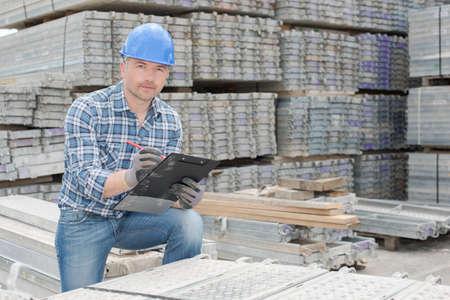 Workman stood with cast concrete slabs