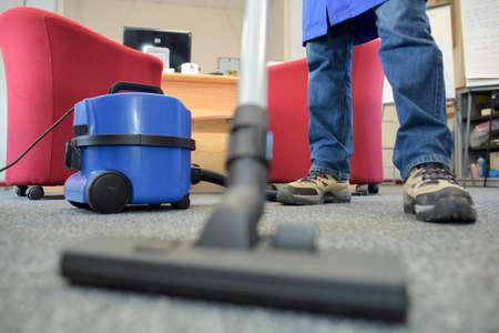 Photo pour Closeup of male feet and vacuum cleaner - image libre de droit