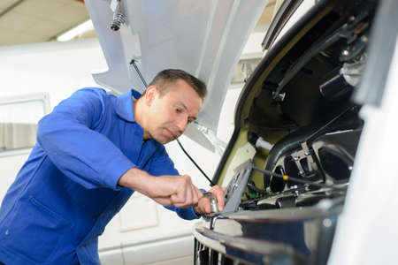 Photo for Mechanic working on front of motor caravan - Royalty Free Image