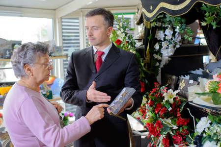 Funeral director showing woman a memorial plaque