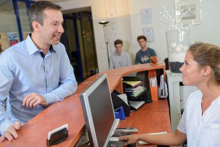 Photo pour Man talking to receptionist - image libre de droit