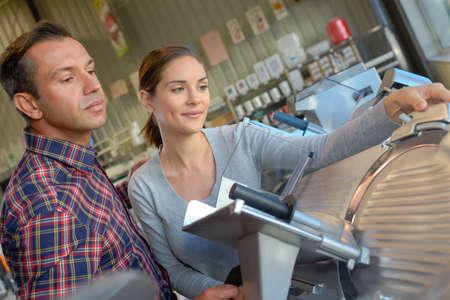 Women looking at industrial meat slicer
