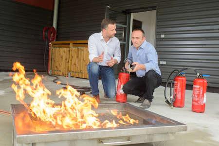 Photo pour Men training with fire extinguishers - image libre de droit