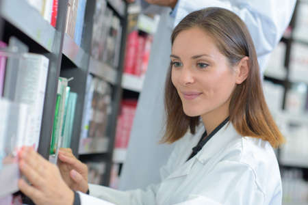 Female medic taking book from shelf