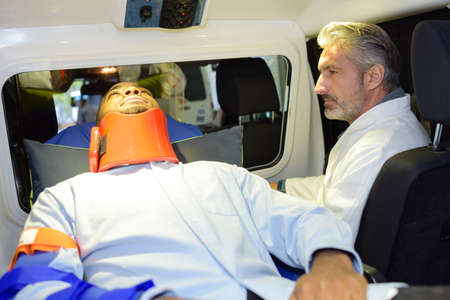 Paramedic in ambulance accompanying man in neck brace