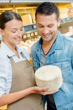 Photo pour Shop assistant showing customer a whole cheese - image libre de droit