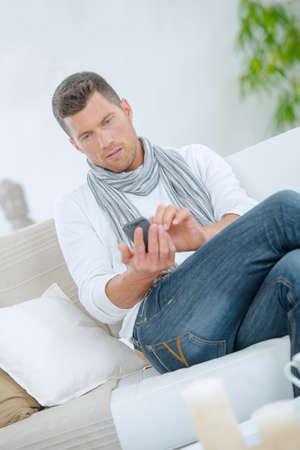 Photo pour Man sending a text message from home - image libre de droit
