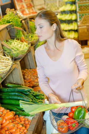 Lady shopping, holding wire basket of vegetables