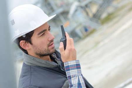 Photo pour Construction worker using walkie talkie - image libre de droit