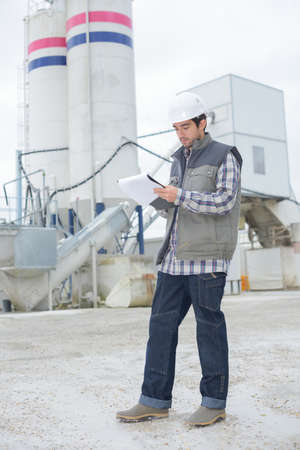 male architect standing near a factory outdoors