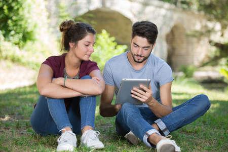 Photo pour young couple using digital tablet at the park - image libre de droit