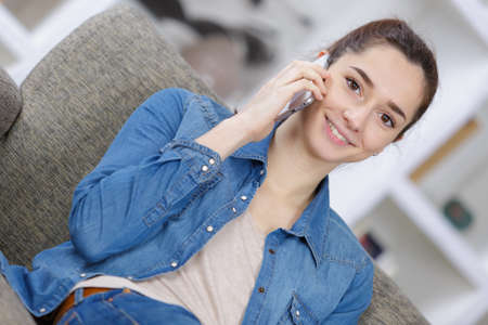 Photo pour smiling teenage girl with smartphone sitting on couch at home - image libre de droit