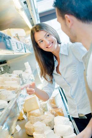Photo pour Couple choosing from cheese counter - image libre de droit