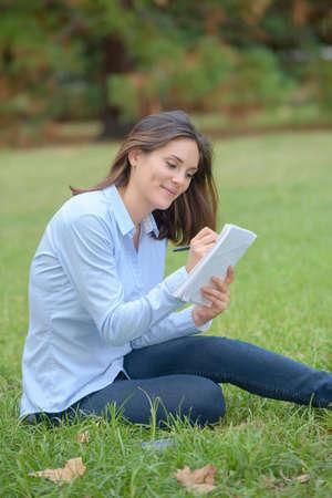 Photo pour Woman sat in park writing in notepad - image libre de droit