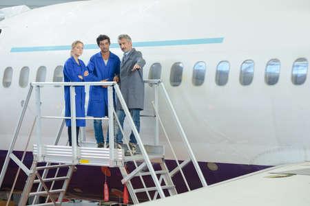 Photo pour People stood on platform beside aircraft - image libre de droit