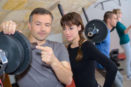 Photo pour trainer explaining how to use training machine in a gym - image libre de droit