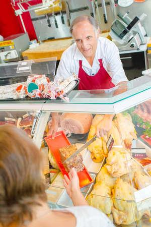 Photo pour Butcher serving a customer with pate - image libre de droit