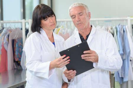 Photo pour Couple in laundry looking at clipboard - image libre de droit