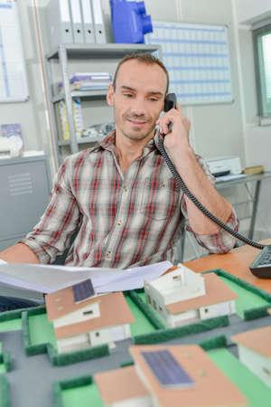 Photo pour Man on telephone, model houses in front of him - image libre de droit