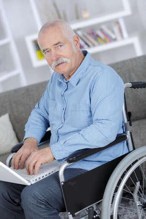Photo pour senior in wheelchair using a computer - image libre de droit