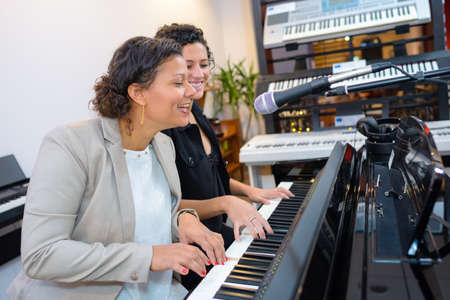 Women playing duet on piano and singing