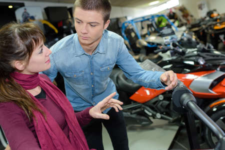 Photo pour Young man and woman talking in vehicle showroom - image libre de droit