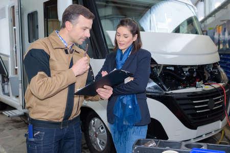 Photo pour Mechanic discussing motorhome repairs with woman - image libre de droit