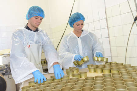 Photo for factory workers preparing tins for canned food - Royalty Free Image