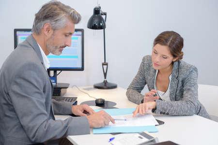 Photo pour Man and woman discussing paperwork in office - image libre de droit