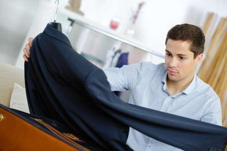 Photo pour close up of businessman packing clothes into travel bag - image libre de droit