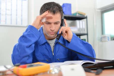 Photo pour Electrician on the phone in his office - image libre de droit