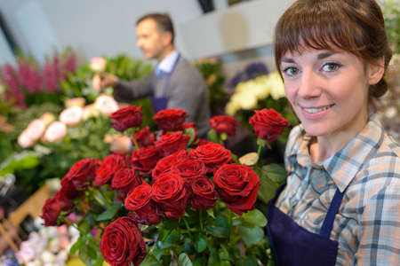 Florist holding bouquet of roses