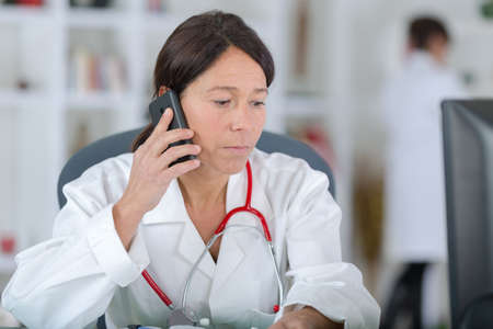 Photo pour portrait of female doctor on the phone in her office - image libre de droit