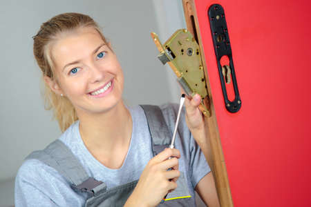 woman locksmith fixing a lock