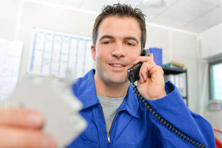 Photo pour Man in overalls on telephone, holding object - image libre de droit